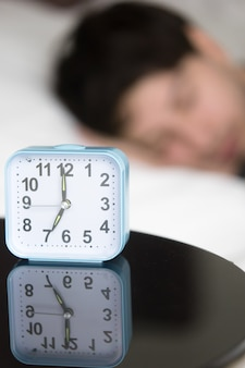 Alarm clock on table in front of sleeping man, vertical