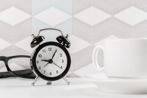 Alarm clock on table with glasses and a cup