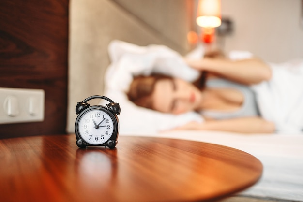 Alarm clock on the table, woman covering her ears with pillow, waking up. morning bedding, girl doesn't want to wake up