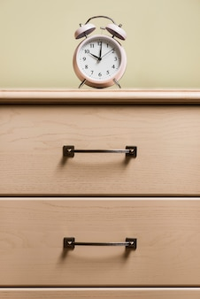 An alarm clock on top of wooden cabinet