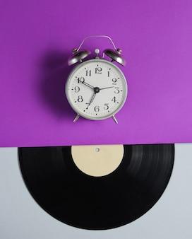 目覚まし時計、紫灰色のテーブルにビニールレコード。レトロなスタイル。上面図