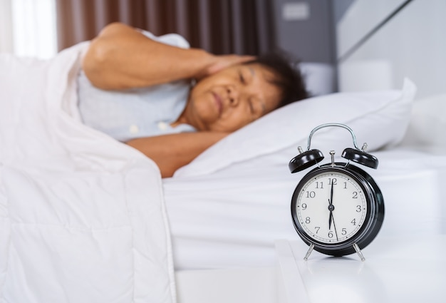 Alarm clock wake up in the morning and senior woman close her ears