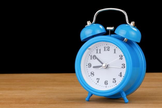 Часы-будильник на деревянном столе