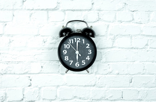 Alarm clock on white bricks