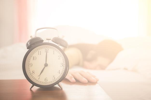 ベッドでバックグラウンドで寝ている女性と目覚まし時計