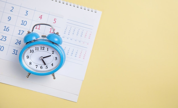 Будильник с календарем на желтом фоне.