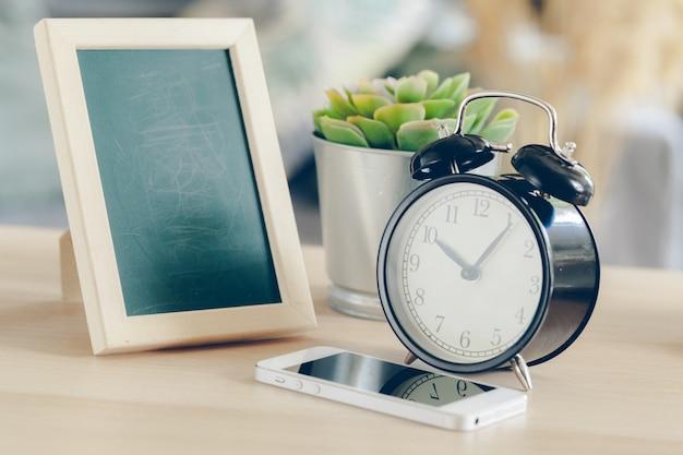 木製のテーブルの上の携帯電話付き目覚まし時計