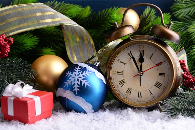 Alarm clock with christmas decorations on color wooden background