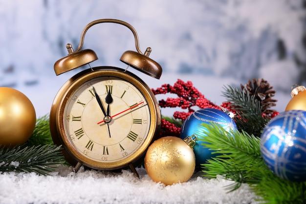 Будильник с рождественскими украшениями на светлом фоне