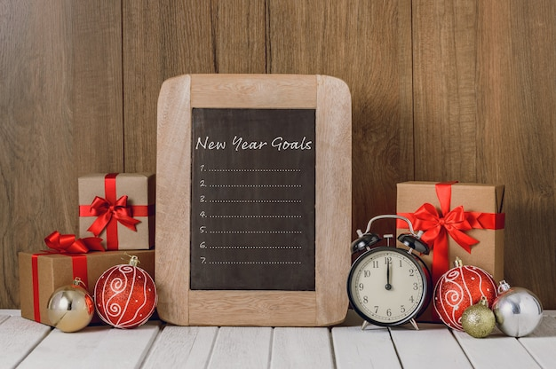 Alarm clock with christmas ornaments and new year's goals list written on chalkboard over wooden background