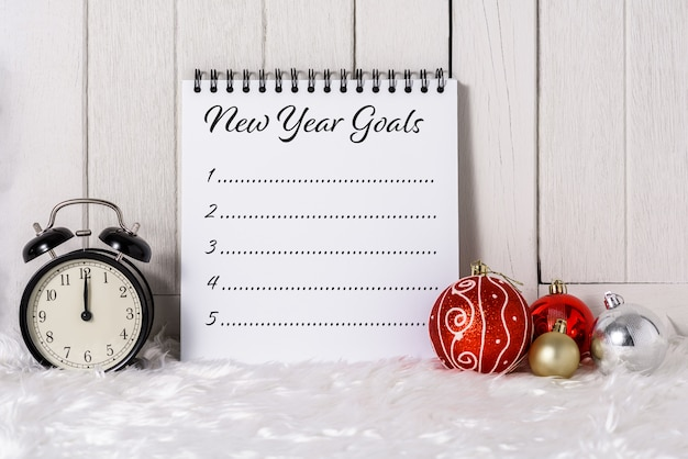 Alarm clock with christmas ornaments and new year's goals list written on notebook with white fur