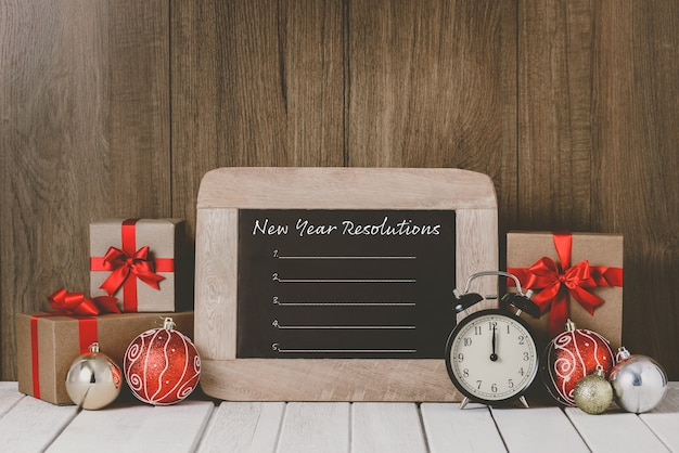 Alarm clock with christmas ornaments and new year's resolutions list written on chalkboard over wooden background