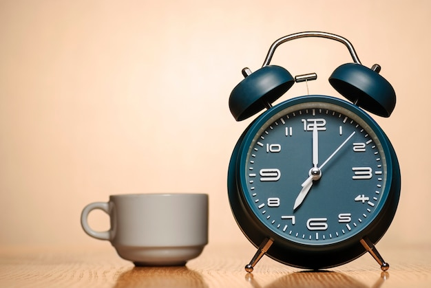 テーブルの上のコーヒーカップ付き目覚まし時計