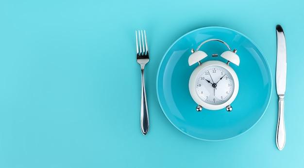 밝은 파란색 배경에 포크와 나이프가 있는 알람 시계. 식사 시간, 아침 식사, 점심 시간 및 저녁 식사 개념. 복사 공간, 배너