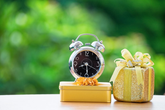 Alarm clock with gift box on green burred background.