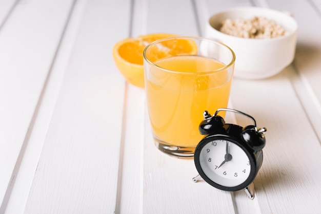 Alarm clock with glass of juice and oatmeal on white table