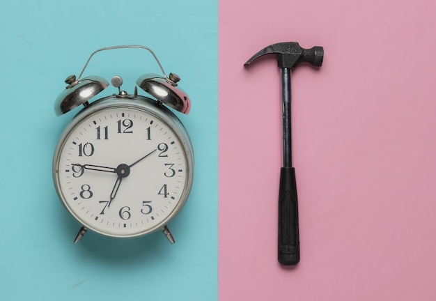 Alarm clock with hammer on pink blue background