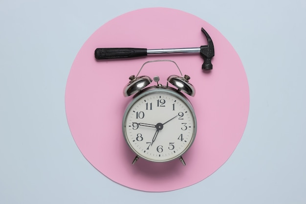 Alarm clock with hammer on white background
