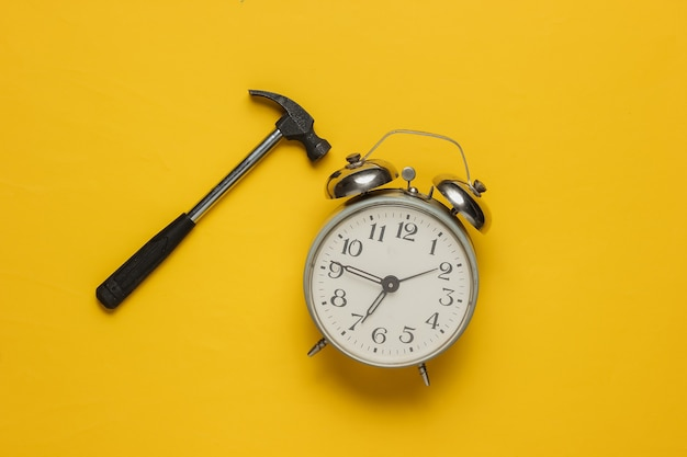Alarm clock with hammer on yellow background