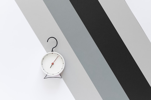 Alarm clock with a hook in the shape of a question mark. background gray, white, black stripes. top view.  copy space.
