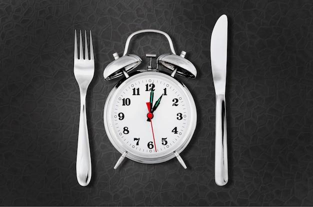 식사 시간 또는 다이어트 개념을 위한 나이프와 포크가 있는 알람 시계