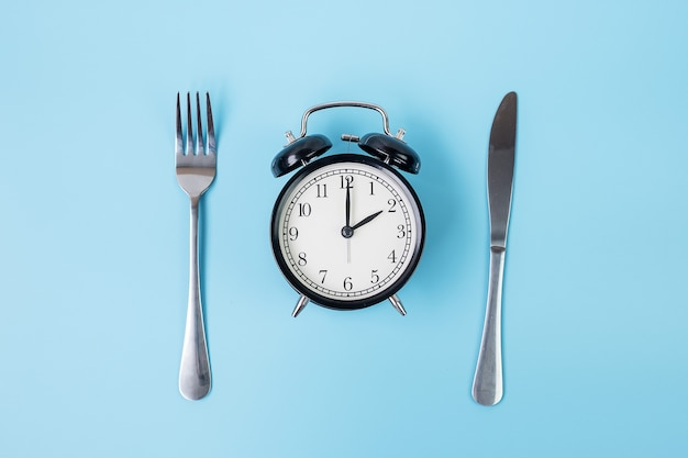 Alarm clock with knife and fork on blue background