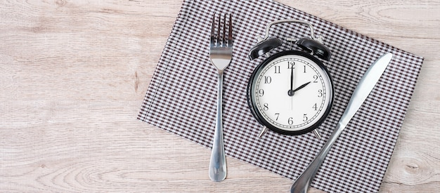 Alarm clock with knife and fork on table cloth background