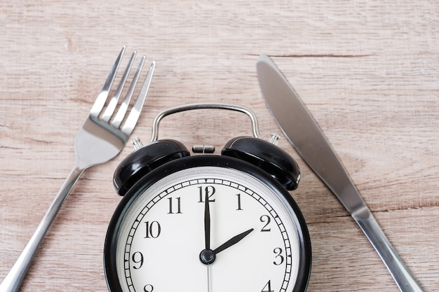 Alarm clock with knife and fork on wooden table background