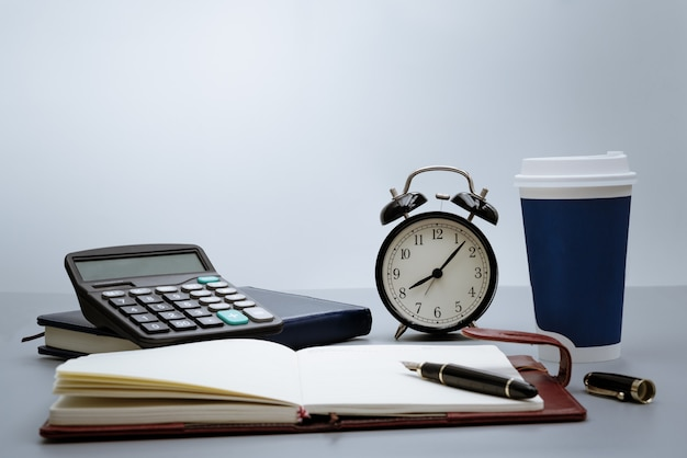 Alarm clock with notebook, calculator, pen and cup of coffee on gray background