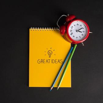 黒の背景にメモ帳と色鉛筆が付いた目覚まし時計学校に戻る素晴らしいアイデア