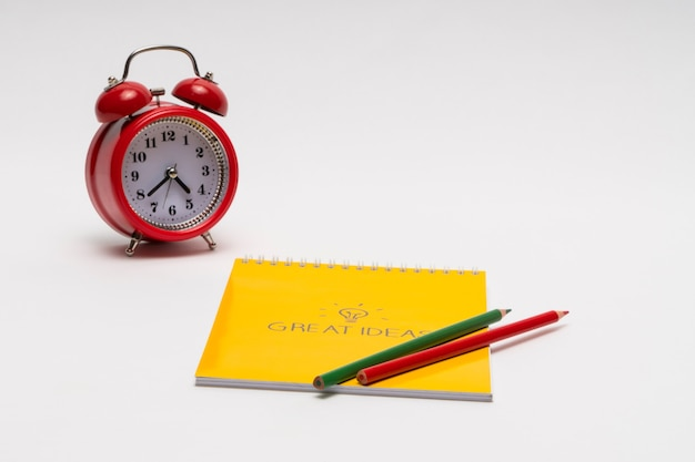 白い背景にメモ帳と色鉛筆が付いた目覚まし時計学校に戻る素晴らしいアイデア