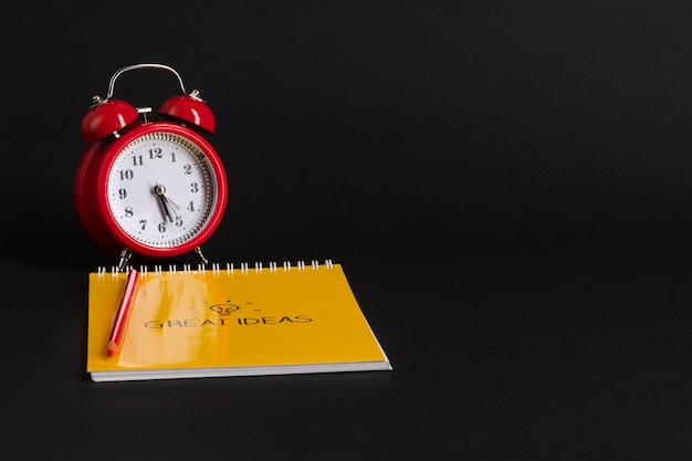 Alarm clock with notepad and colored pencils on black background back to school great ideas