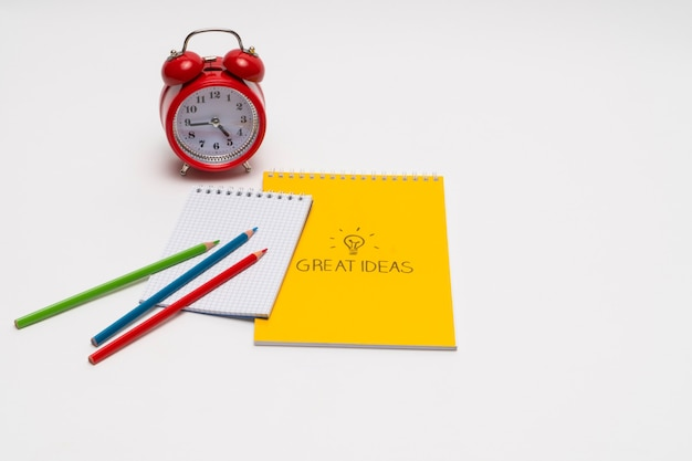 Alarm clock with notepad and colored pencils on white background back to school great ideas