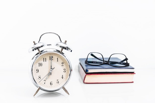 Alarm clock with old book with eyeglasses