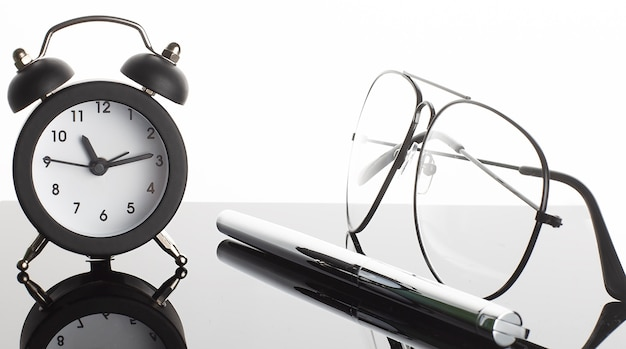 Alarm clock with pen and glasses on mirror black table and white black background