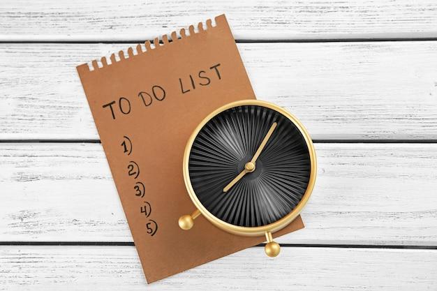 Будильник со списком дел на деревянном. концепция управления временем