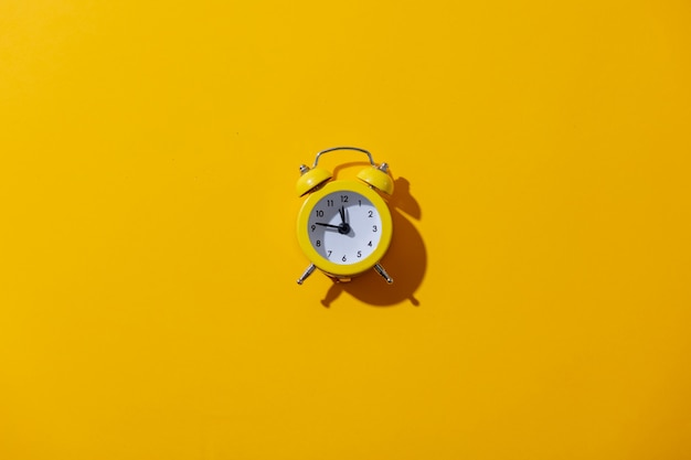 Alarm clock with two bells on yellow background
