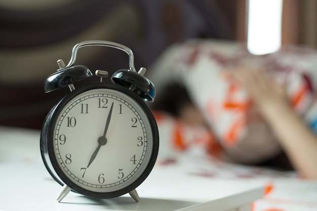 Alarm clock ,woman lazy to wake up to work on the bed.