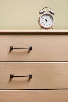 Alarm clock on wooden closed drawer