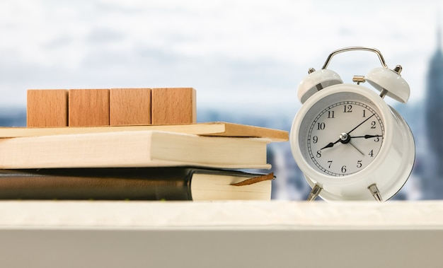 Alarm clock and wooden cubes on books on a table