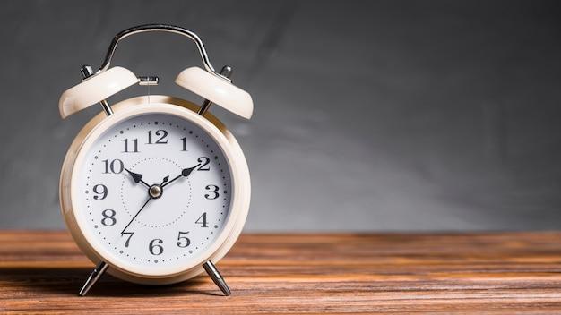 Alarm clock on wooden desk against gray background