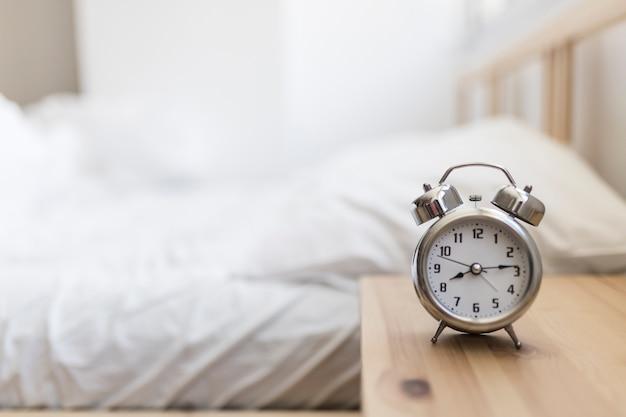 Alarm clock on wooden desk in bedroom