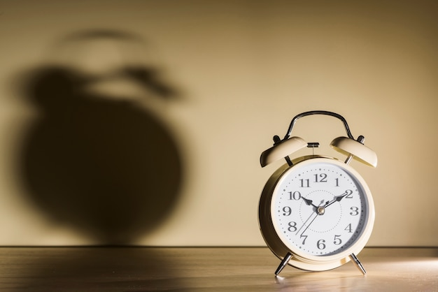 Alarm clock over wooden desk with shadow on wall