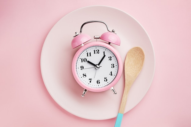 Alarm clock and wooden spoon on empty pink plate.