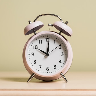 An alarm clock on wooden surface