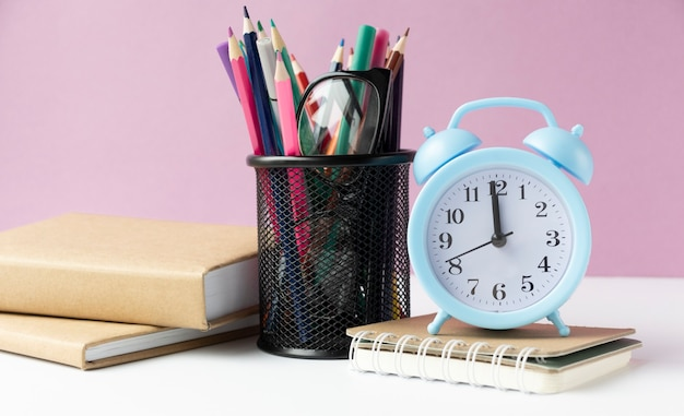 Alarm clock on wooden table on background in classroom, back to school concept