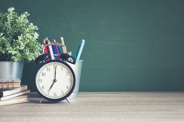 Alarm clock on wooden table on blackboard background in classroom
