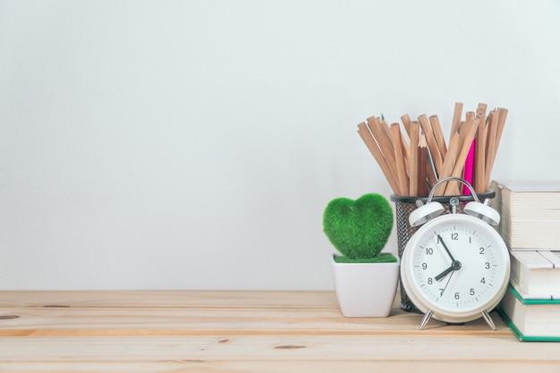 Alarm clock on wooden table on concrete wall blackboard background
