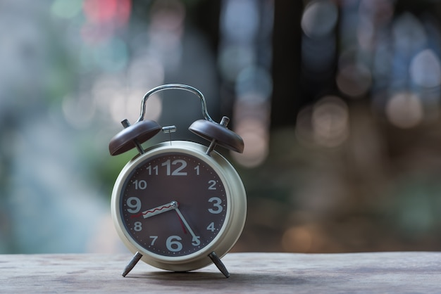 Alarm clock on wooden table with green nature bokeh background.