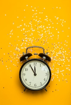 Alarm clock on a yellow  background with festive glitter. new year eve minimal background concept.